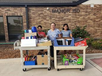 Anya Satija presents school supplies to Manor ISD