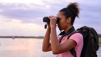 Corina Newsome (black woman) holds binoculars wearing a backpack. The marsh is visible in the background.