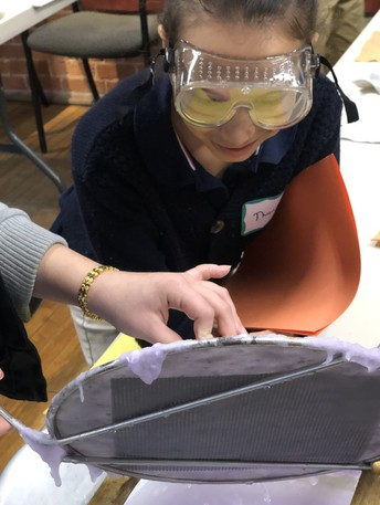 female student wearing goggles making paper