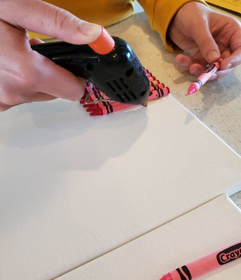 Glue crayons on surface with glue or glue gun.