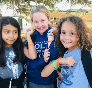 three students showing perfect attendance bracelets