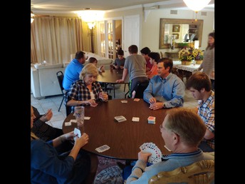 The Eppes' family playing card games on one table and LRC on the other.