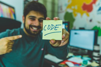 Man holding sign that says code in front of computer and monitors (Photo by Hitesh Choudhary on Unsplash)