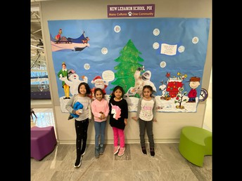 Our 2nd Graders show Holiday Pride in front of our Festive Bulletin Board