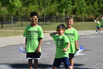 students on playground at Magnolia with matching t-shirts