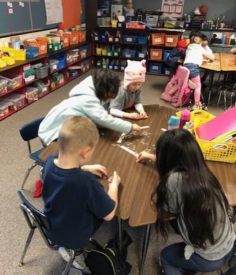 Kindergarten students counting Pennies for Patients.