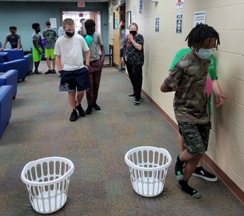 2 white laundry baskets are in the foreground; students are spaced throughout the room behind the baskets  with balloons behind their backs