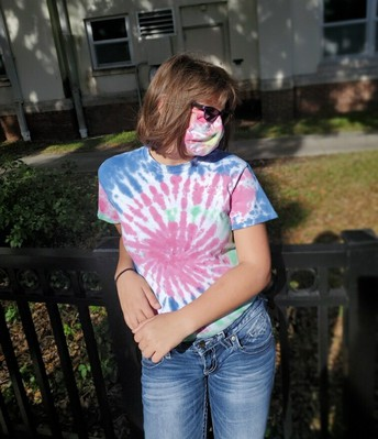 Teagan poses while leaning against a fence, wearing sunglasses, her matching tie-dyed mask and shirt, and jeans