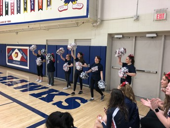 Members from UHS Sparkle Cheer Team perform at a basketball game