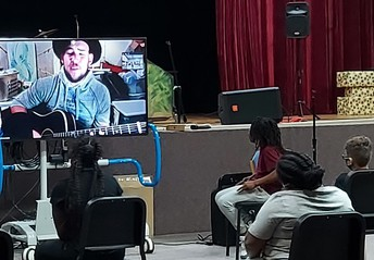 Students listen intently while James Durbin is on Zoom screen with his guitar