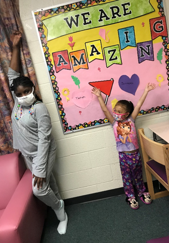 2 girls wearing masks with hands excitedly in the air; bulletin board says We Are Amazing