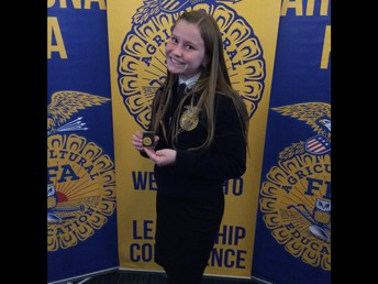 Delanie Christensen poses with Izzy Taft's state pin for Plant Systems AgriScience Fair Division winner.