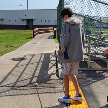 Fisher walking along a warning track on the sidewalk