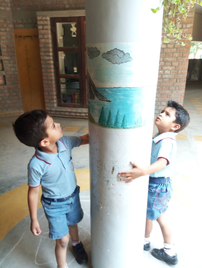 Figure 1: 2 boys looking at a graphic pasted on a concrete column on the outside of a school.