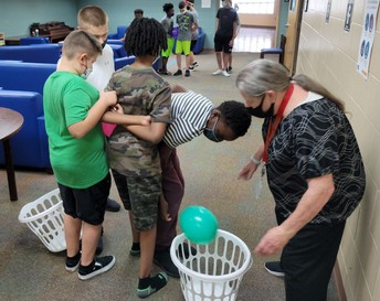 4 boys racing to put their balloons in the laundry baskets; a dorm staff member stands ready to help