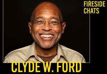 Clyde Ford is wearing silver rimmed glasses and a large smile against a black backdrop.