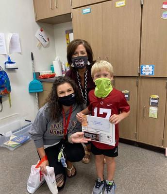 Mrs. Tyner, Mrs. Osburn, and student holding certificate