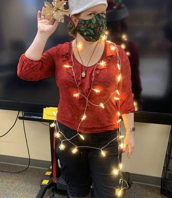 Ms. Norman dressed in reindeer antlers with white Christmas lights wrapped around her body