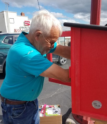 Picture of Dennis Biller stocking free little library.