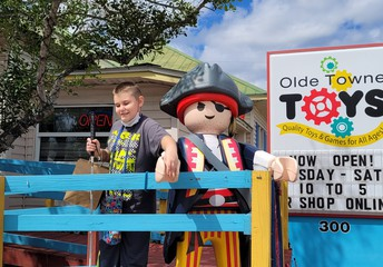 Brody standing next to a life-size pirate-themed Lego figure; Olde Towne Toys sign is behind them