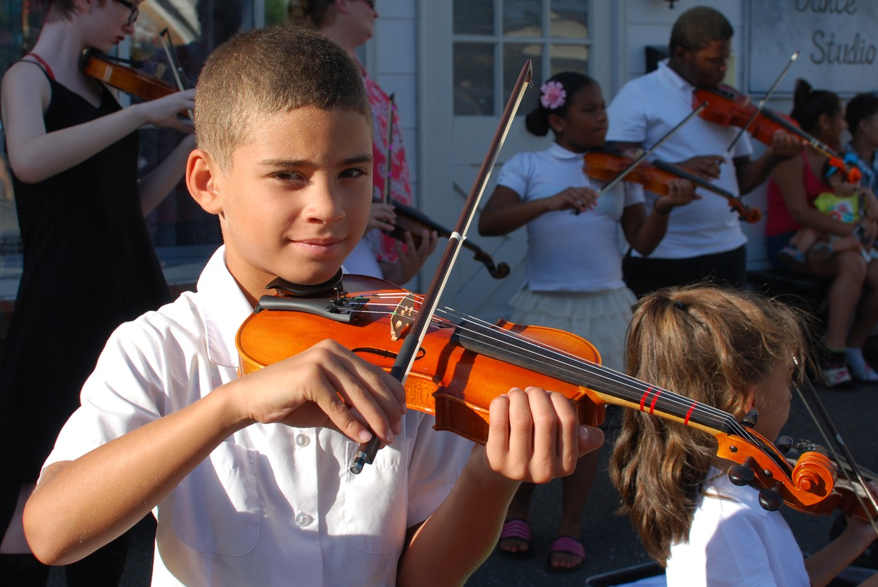 Boy playing the violin during the summer strings program last year.