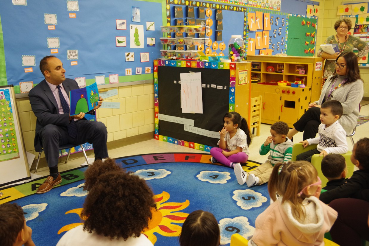 Dr. Zrike reading to a group of Pre-K students at circle.