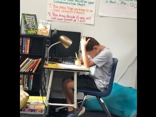 A student hard at work editing his writing.