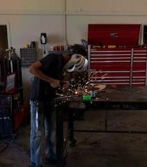Peyton Hinkley working with metal.