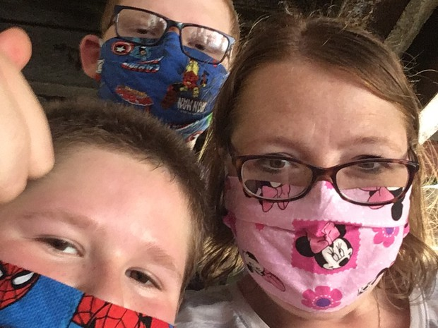 Kara Theriaque  with her two sons wearing their masks.