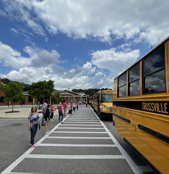 SCHOOL BUSES LEAVING PAINE ON FINAL DAY, TEACHERS WAVING, CLOUDY BUT SUNNY SKIES