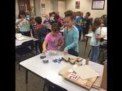 Students using cardboard and duct tape to create a Ghost Trap.