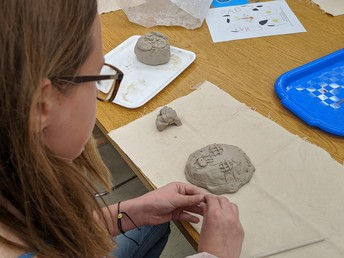 Chardon Middle School 5th-grade student works on her clay face mask designed to be a sloth.