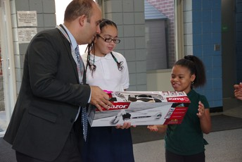Dr. Zrike delivering a Razor Scooter to a math summer challenge winner at McMahon.
