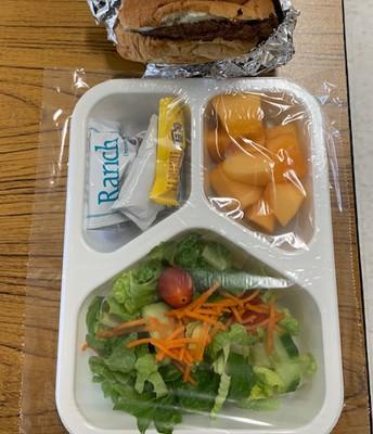 Cheesburger with fresh salad and cantaloup