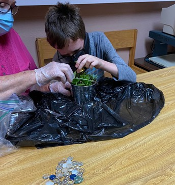 Student is potting his plant while a staff member assists