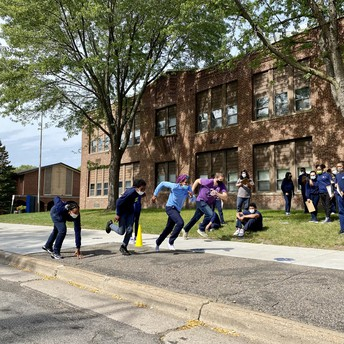 Students race outside while others watch and take notes.