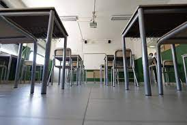 Empty desks spaced apart in a classroom