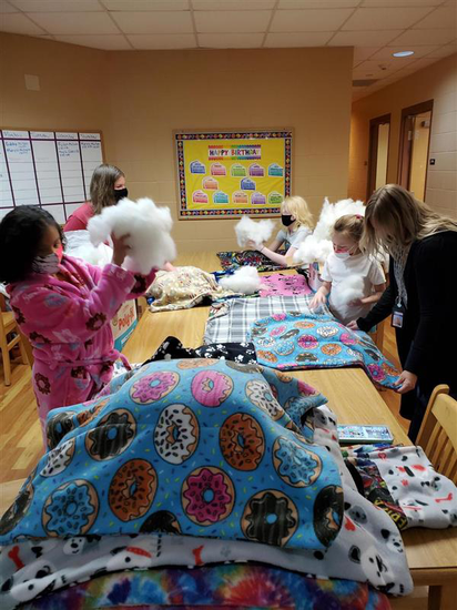 Middle school girls gather around a long table. there are many rectangles of colorful, soft fabric waiting to be stuffed with polyester fiberfill stuffing. The girls are dressed in their pajamas and wearing their masks.
