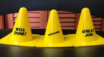 """three yellow constructions cones labeled """"well done"""" """"awesome"""" and """"great job"""""""