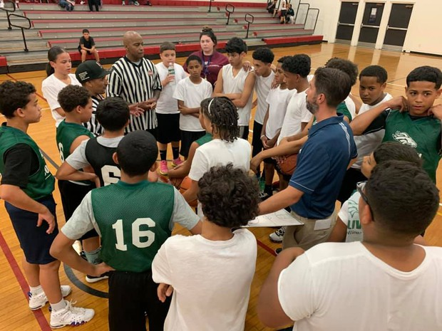 A huddle of middle school basketball Peck and Kelly student athletes before a game.