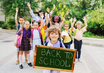 Boy holding a back to school sign with classmates behind him.