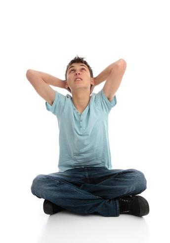 Boy grabbing head, looking upward in distress