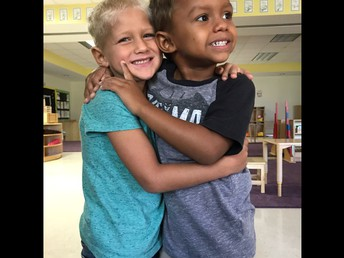 Two boys smiling and hugging.