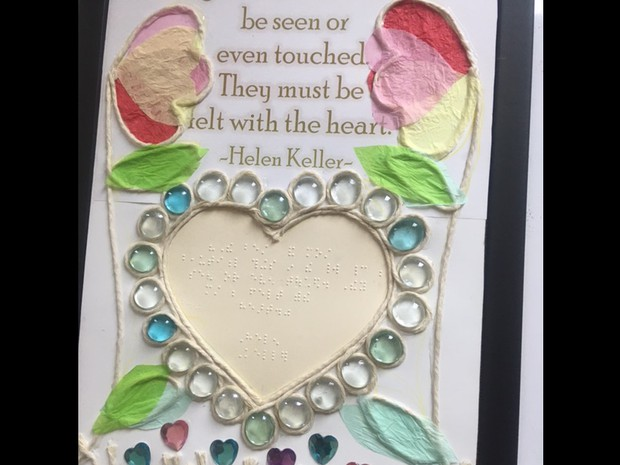 Tactile heart with twine and smooth stones outlining; twine and tissue paper flowers on both sids of poster; Helen Keller Quote: The best and most beautiful things can't be seen or even touched. They must be felt with the heart.