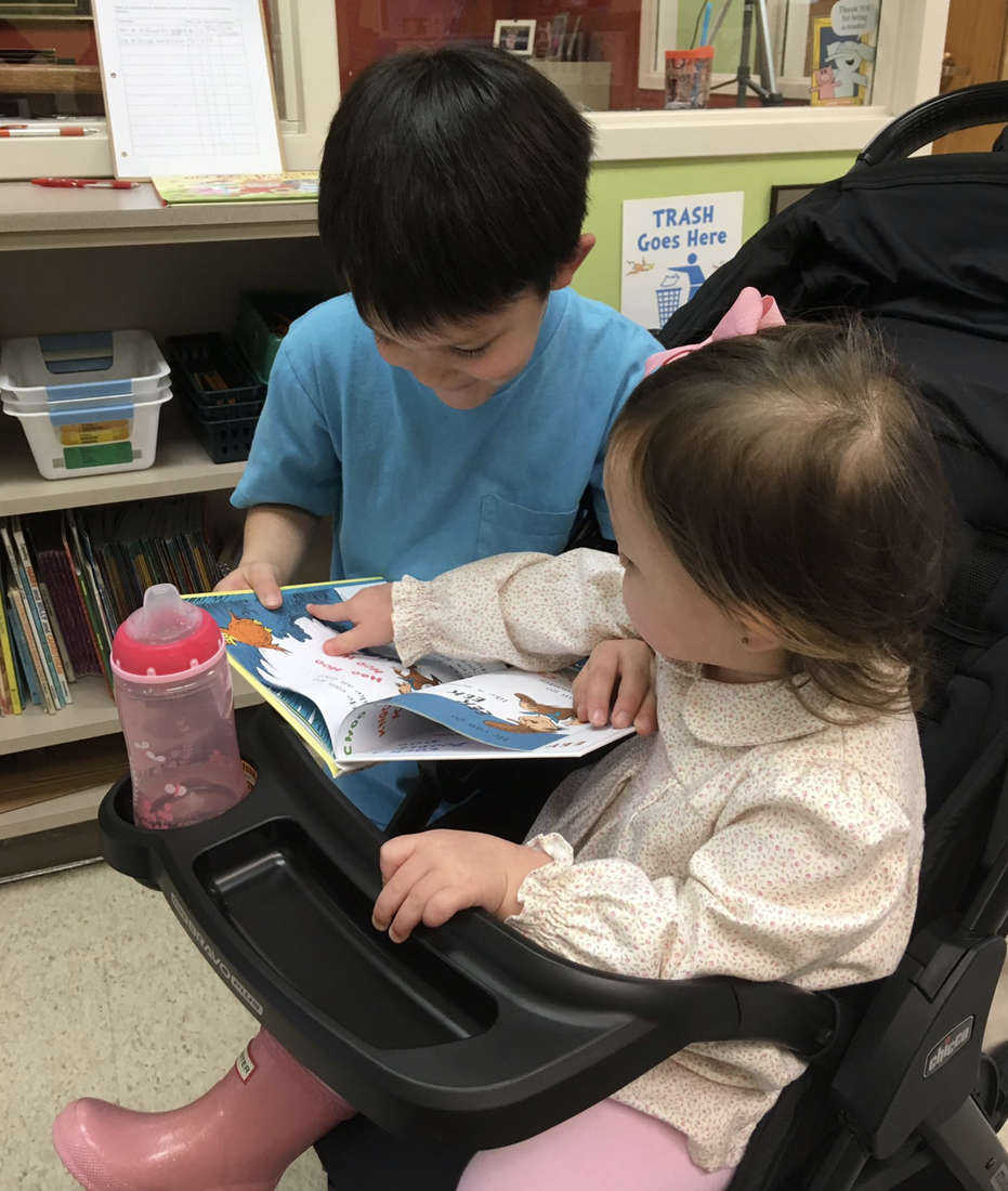 CCPS student sharing a book from the Book Fair with his sibling.