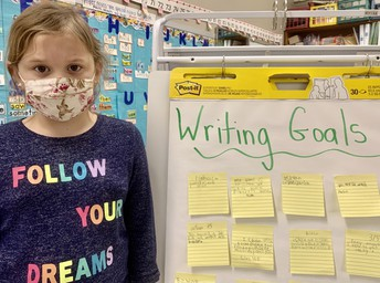 Student in front of writing goals board