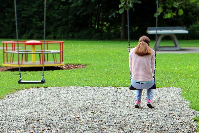 Sad teen girl sitting on a swing
