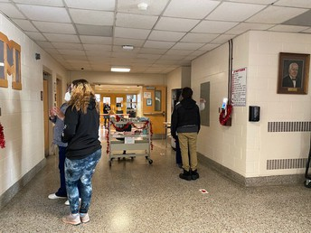Mrs. Curran-Paller and Nurse Gilman helping students to go through the scanning process.