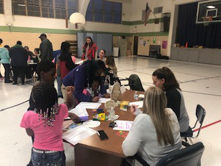 Scholars and families participating in literacy activities.