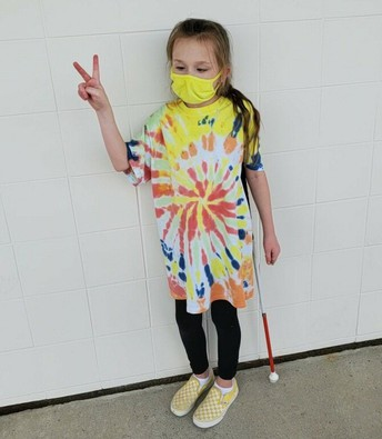 Kayla showing her tie-dyed shirt of yellow, orange, white and small bits of navy blue; she's holding her fingers up in a peace sign